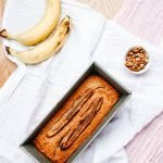 Easy Oatmeal Banana Bread with walnuts and some additional bananas on the side.
