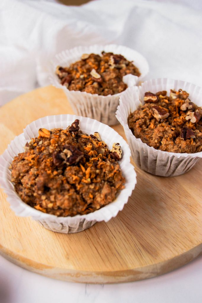 Three Healthy Carrot Cake Muffins placed on a wooden board