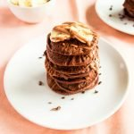 Healthy Chocolate Banana Pancakes served with Banana, Maple Syrup and Cacao Nibs.