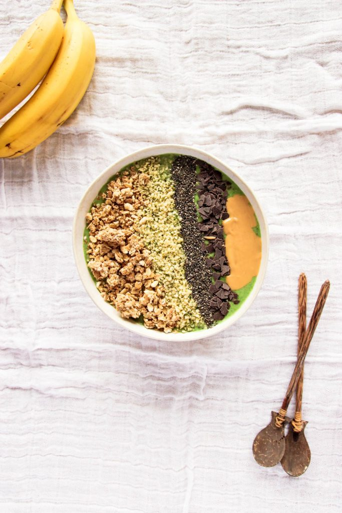 Green Smoothie Bowl decorated with wooden spoons and banana on the side