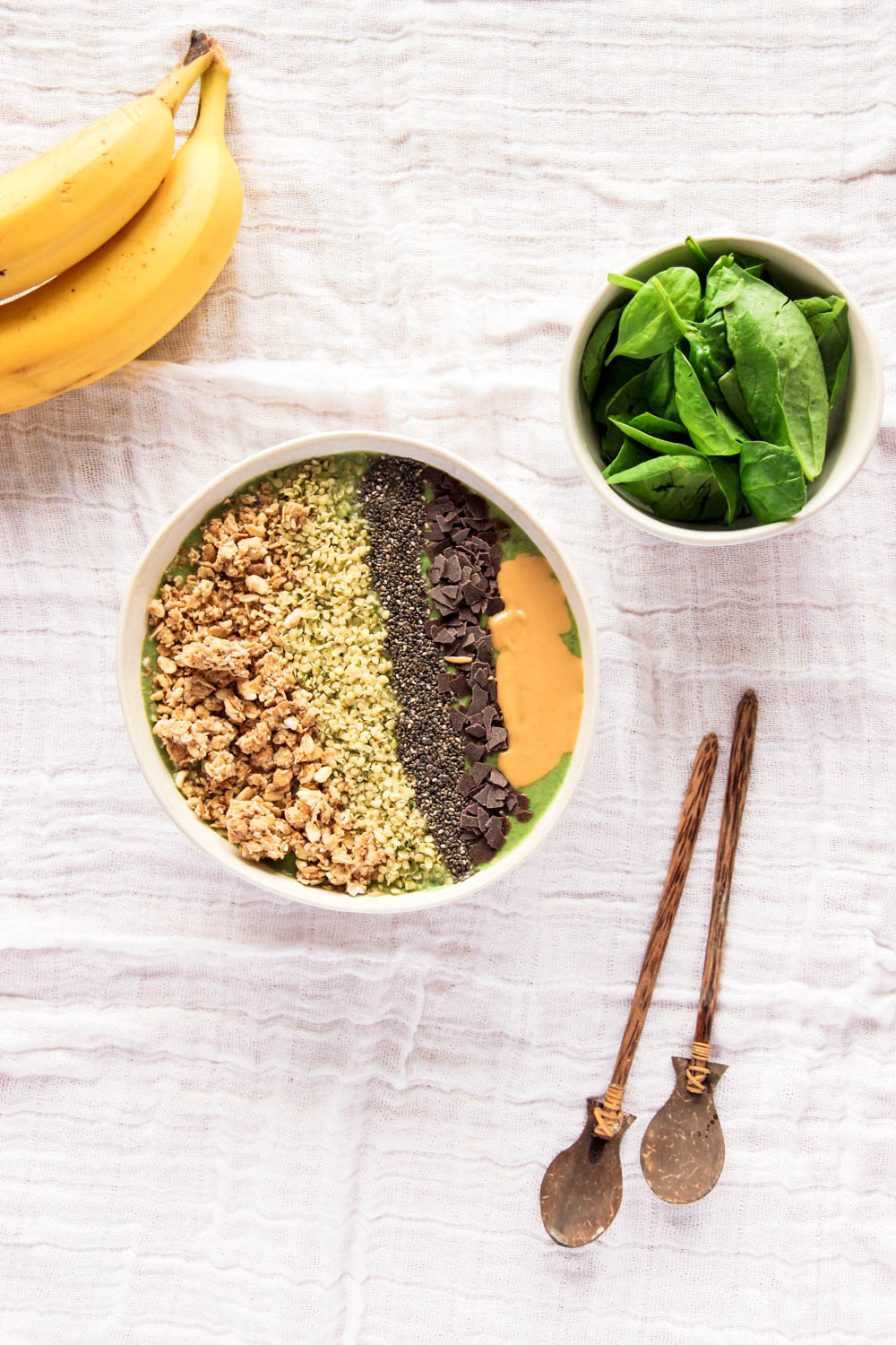 Green Smoothie Bowl decorated with wooden spoons and banana as well as spinach on the side
