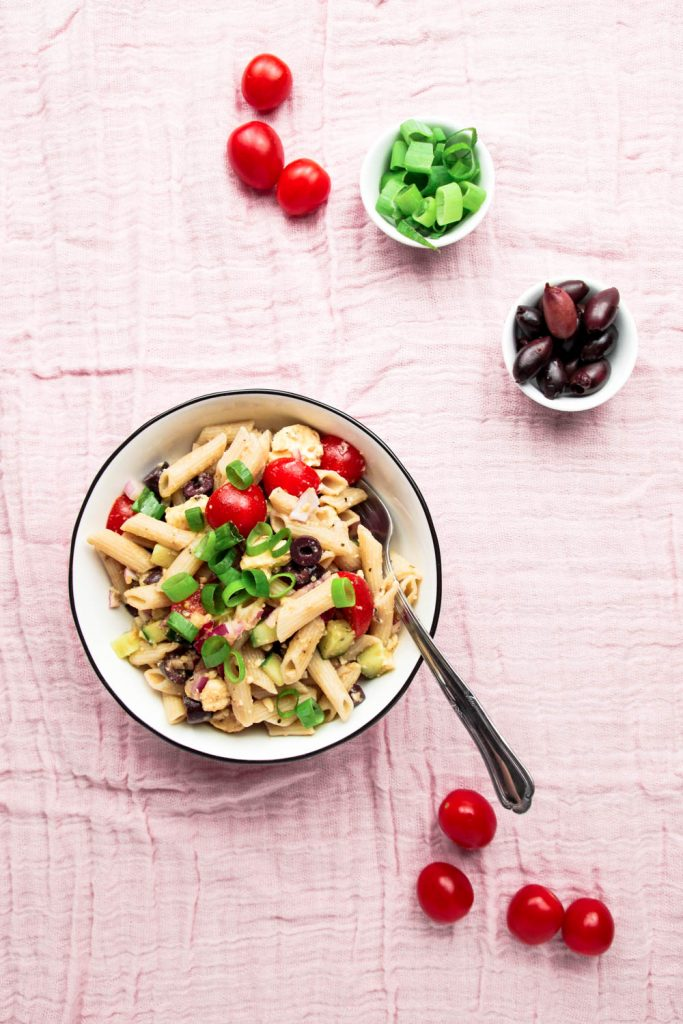 Fresh Summer Pasta Salad with tomatoes, olives and spring onions on the side.