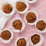 Healthy Pumpkin Muffins placed on a pink and white surface.