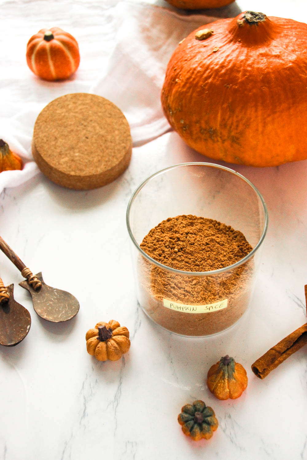 Pumpkin Pie Spice Blend in a jar with cinnamon, wooden spoons and pumpkin on the side.