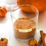Pumpkin Pie Spice Blend in a jar with cinnamon and pumpkin on the side.