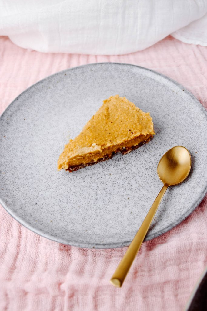 Vegan Pumpkin Cheesecake served and sliced up on a grey plate.