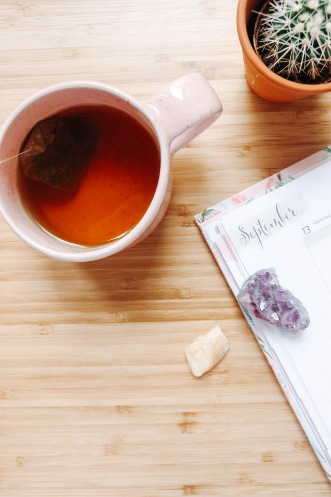 A cup of tea next to a cactus, a planner and some crystals